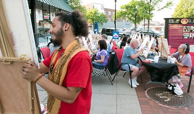 05/25/18  Wesley Bunnell | Staff  Artist Christian Yong points out examples of his work for the crowdled a painting class on Friday night outside of KC's on Main which also featured waiter service and food from KC's. The program is called Patio Paint & Sit.