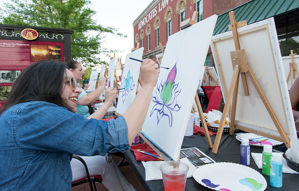 05/25/18 Wesley Bunnell | Staff Maria Morales paints during an outdoor art class taught by artist Christian Yong on Friday night outside of KC's on Main. The program also featured waiter service and food from KC's and is called Patio Paint & Sit.