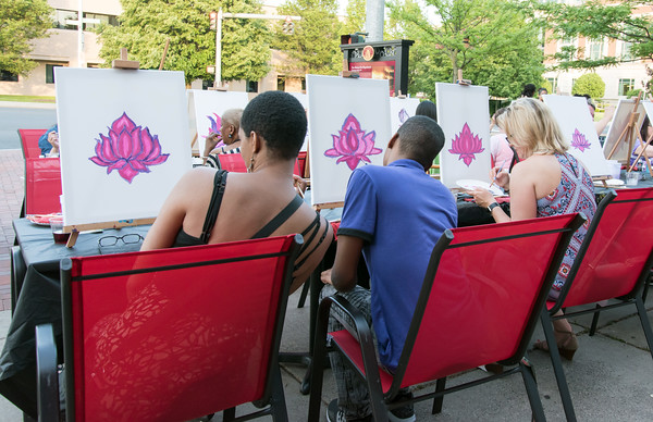 05/25/18 Wesley Bunnell | Staff Four different interpretations of a flower from students in artist Christian Yong's painting class on Friday night outside of KC's on Main. The program featured waiter service and food from KC's and is called Patio Paint & Sit.