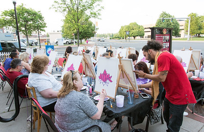 05/25/18  Wesley Bunnell | Staff  Artist Christian Yong, R, led a painting class on Friday night outside of KC's on Main. The program also featured waiter service and food from KC's and is called Patio Paint & Sit.