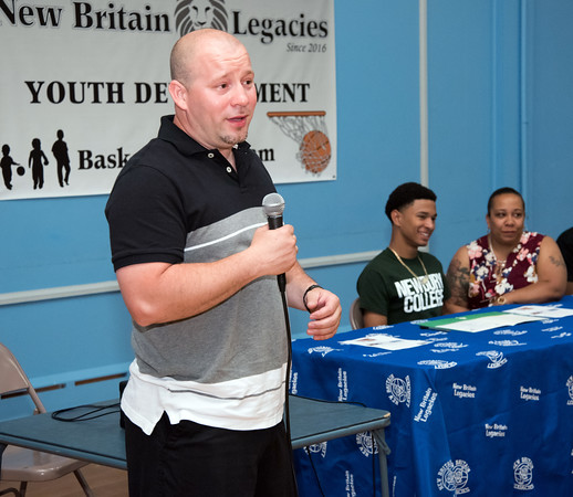 05/25/18 Wesley Bunnell | Staff Francisco Santiago Sr speaks at the signing of his son Francisco Santiago II from E.C. Goodwin High School to attend and play basketball for Newbury College. Santiago's mother Marsha Michaud sits to his right.