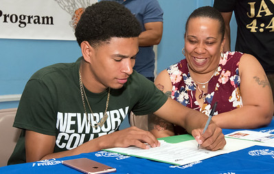 05/25/18  Wesley Bunnell | Staff  Basketball standout at E.C. Goodwin High School Francisco Santiago II signed his papers intending to attend and play basketball for Newbury College as his mother Marsha Michaud smiles.  The signing took place at St. Matthew's on Friday night.