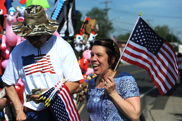 5/26/2018 Mike Orazzi | Staff Tina Calafiore buys and American flag from Bruce Romanoff during the Berlin Memorial Day Parade on Saturday along Farmington Avenue.