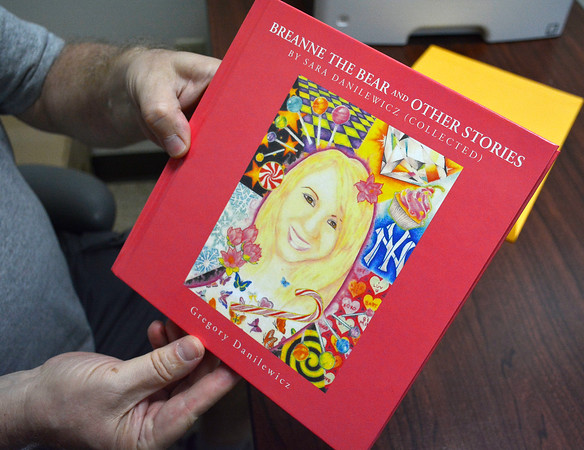 5/31/2018 Mike Orazzi   Staff Gregory Danilewicz holds a book of stories written by his daughter Sara.