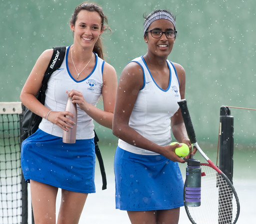 05/03/18 Wesley Bunnell | Staff Bristol Eastern's tennis players including Amy Bhagaloo, R, smile as they walk off the court during a sudden rain storm in practice before their matches against Newington on Thursday afternoon.