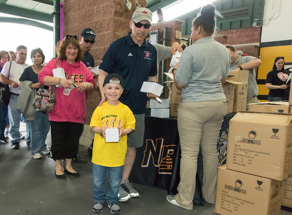 05/04/18 Wesley Bunnell | Staff Tim Filon and son Ryan, age 4, receive their Mayor Erin Stewart bobblehead doll while entering New Britain Stadium on Friday night. The New Britain Bees played the Road Warriors for their first home game of the season.