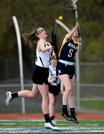 5/8/2018 Mike Orazzi | Staff RHAM's Amanda Jacobson (5) and Bristol Co-Op Lacrosse's Ashley Watson (14) during girls lacrosse at BEHS Tuesday.