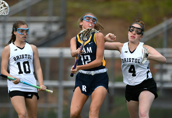 5/8/2018 Mike Orazzi | Staff RHAM's Shannon Romeo (12) and Bristol Co-Op Lacrosse's Erika Santilli (4) during girls lacrosse at BEHS Tuesday.