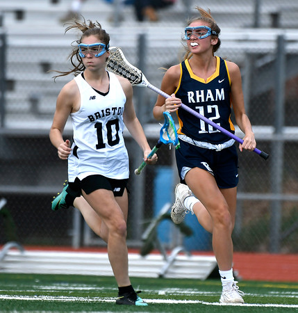 5/8/2018 Mike Orazzi | Staff RHAM's Shannon Romeo (12) and Bristol Co-Op Lacrosse's Lily Hansen (10) during girls lacrosse at BEHS Tuesday.