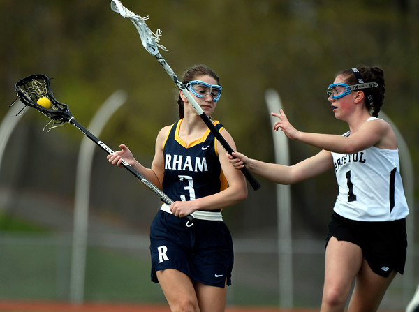 5/8/2018 Mike Orazzi | Staff RHAM's Mia Rhodes (3) and Bristol Co-Op Lacrosse's Jenna Lowe (1) during girls lacrosse at BEHS Tuesday.