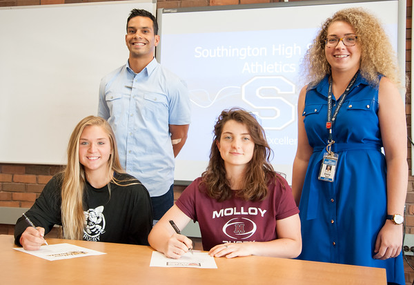 05/30/18 Wesley Bunnell | Staff Southington rugby players Brooke Garcia and Kaitlyn Demaio sign thier letters of intent on Wednesday afternoon to attend and play for American International University and Molloy College. Head coach Nick Vargas, back rear and assistant coach Emily Reed.