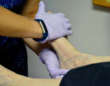 5/30/2018 Mike Orazzi | Staff APN Georgia Sterpka examines Marcia Lawrence's feet while at the Bristol Senior Center on Wednesday morning.
