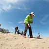 JIM VAIKNORAS/Staff photo Plum Island residence Clare Williams plants sea grass along along Reservation Terrace in an effort to preserve the dune from erosion.