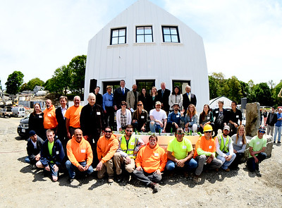 JIM VAIKNORAS/Staff photo Workers and officials pose in front of a 3/4 prototype building at the ground breaking of Hillside Center for Sustainable Living in Newburyport Friday.