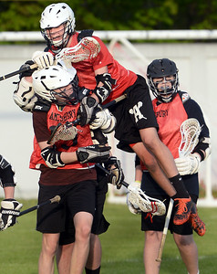 CARL RUSSO/Staff photo. Amesbury's Zachariah Daniels jumps on top of Leif Riley to celebrate Riley's goal. His goal was the first one of the game. This year Amesbury High School sponsored boys lacrosse for the first time, and the program competed at the JV level for its inaugural season. Monday night the program celebrated its first ever senior night, honoring it only senior, Carter Castay and his family. 5/14/2018