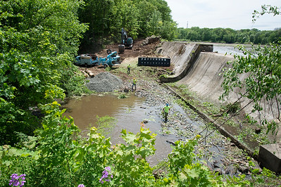 05/23/19  Wesley Bunnell | Staff  Workers remove debris from an area of the Kensington Dam on Thursday afternoon. which was drained.