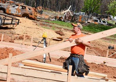Michael Richardson carries a piece of lumber at a construction site on Ramada Lane Wednesday in Paradise. (Matt Bates -- Enterprise-Record)