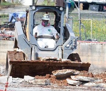 A worker cleans up broken concrete Wednesday in Paradise. (Matt Bates -- Enterprise-Record)