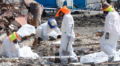 Workers wear protective suits while sifting through debris off of Pearson Road Wednesday in Paradise. (Matt Bates -- Enterprise-Record)