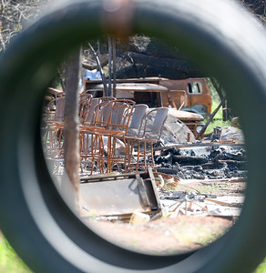 A tire swing frames fire destuction off of Sawmill Road Wednesday in Paradise. (Matt Bates -- Enterprise-Record)