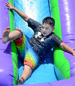 KEVIN HARVISON | Staff photo Edmond Doyle student Ethan Carney slides down the inflatable water slide during the last day of school Fun Day.