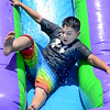 KEVIN HARVISON | Staff photo<br /> Edmond Doyle student Ethan Carney slides down the inflatable water slide during the last day of school Fun Day.