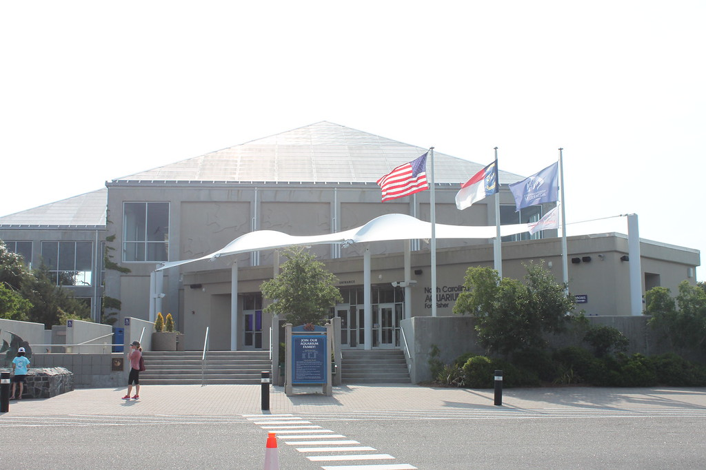 North Carolina Aquarium at Fort Fisher, a building has three flags in the front