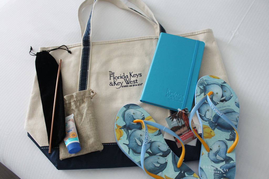 Reef safe sunscreen, a reusable straw, flip flops, and notebook