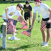 KEVIN HARVISON | Staff photo<br /> Pictured from left, members of the McAlestser High School football team, Lleyton Bass, Luke Homer and Trevor Capps, help put out U.S. Flags on grave sites at Oak Hill Cementary Friday.