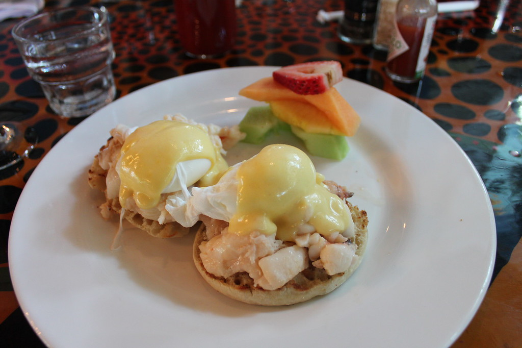 A white plate has a stack of fruit with eggs benedict topped with lobster