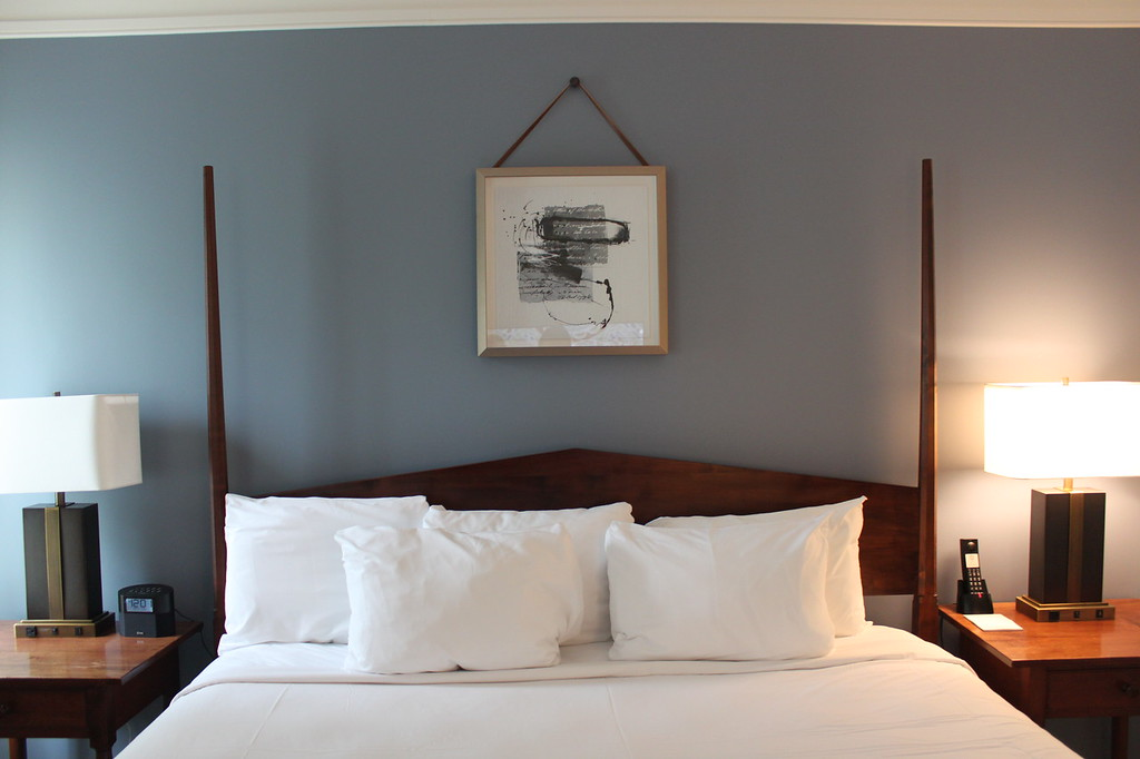 Wood bed frame with white pillows and artwork at Williamsburg Lodge