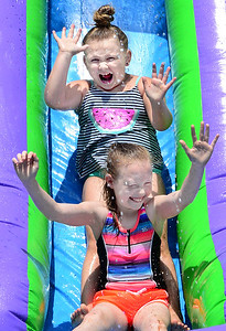 KEVIN HARVISON | Staff photo Edmond Doyle students Addyson Pennington, top and Tenley Waller react as they go down the inflatable water slide during the last day of school, Fun Day.