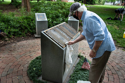 Davidson resident and former Marine Bob Doran helps clean the WWII memorial at the Davidson College War Memorial prior to the placing of flags around the memorial. [Bill Giduz photo]