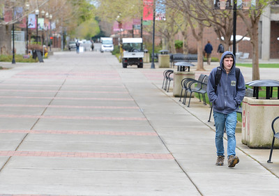 Chico State senior Paul Curtis walks through a virtually empty Chico State campus on March 18. Curtis remained on campus during the shut down to work at his job at Chico State IT Support Services. (Matt Bates -- Enterprise-Record File)
