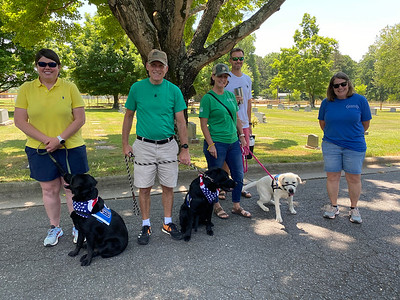 """Two puppies in training with Continuing the Mission (CTM) and the organizaitons """"Ambassador"""" were on hand Sunday as Scouts, JROTC Cadets, and volunteers gathered to place flags on the graves in the three cemeteries across town."""