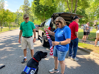 Suzy Lutz folds a star spangled bandana for Trane - a service dog in training. Retired Lieutenant Colonel Tim Stroud and his wife are fostering Trane.