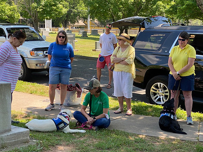 """Suzy Lutz (blue t-shirt) is a co-founder of Continuing the Mission, a Davidson-based nonprofit that trains and provides service dogs to Veterans with PTSD. Three CTM dogs were on hand for the """"Flags In"""" event."""