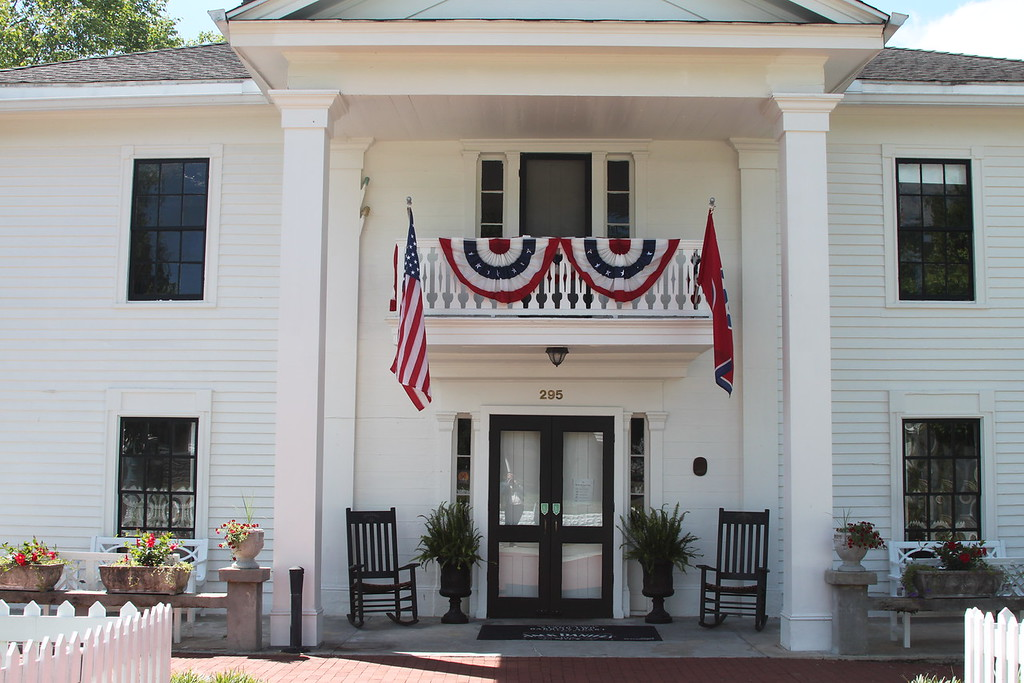 An old white house has the American and Tennessee flags and two black rocking chairs, Miss Mary Bobo's