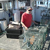 SEAN HORGAN/Staff photo/Joe Mondello, as with many lobstermen at docks around Gloucester and the rest of Cape Ann, wasted little time getting back to work after the state lifted a ban on lobster trapping on Friday. The 71-year-old was getting his traps ready on the Everett Jodrey State Fish Pier before heading to sea on his Tully IV behind him