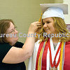 Julie Kobold (left) helps Courtney Kobold with her tassel ahead of Friday's commencement at Hall High School.