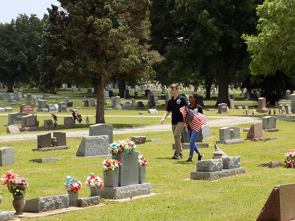 MIKE ELSWICK/Muskogee Phoenix Tonie Allen, left and Taraji Cooper walk among graves at Greenhill Cemetery on Thursday afternoon looking for graves of military veterans.