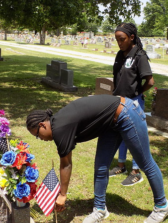 MIKE ELSWICK/Muskogee Phoenix Muskogee High School Air Force ROTC student Gianna Thompson places a flag on a veteran's grave Thursday while fellow student Taraji Cooper looks on.