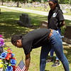 MIKE ELSWICK/Muskogee Phoenix<br /> Muskogee High School Air Force ROTC student Gianna Thompson places a flag on a veteran's grave Thursday while fellow student Taraji Cooper looks on.