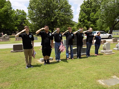 MIKE ELSWICK/Muskogee Phoenix Some of the 28 Muskogee High School Air Force ROTC students involved in placing American flags on the graves of veterans at Greenhill Cemetery salute after a flag was placed.