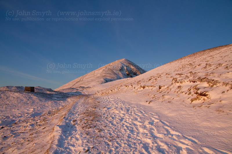 The winter sunrise turns the snow on Croagh Patrick pink on a winter's morning just before Christmas Day in 2010. There was a particularly cold spell that winter, and the temperature at the base of the mountain was -10 celcius.