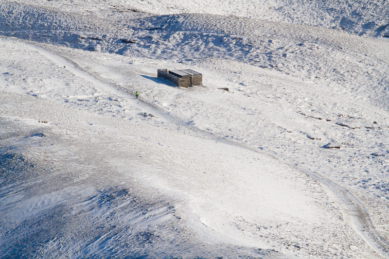 A lone hill runner jogging in the snow, up to the summit of Croagh  Patrick in Co. Mayo, Ireland early in the morning just before Christmas Day, 2010.