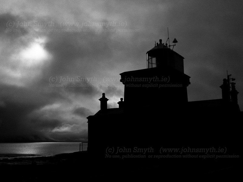The lighthouse at Black Sod at the tip of the Mullet peninsula is silhouetted against a cloudy sky. A plaque nearby states that it was a weather forecast given from this station in 1944 that helped decide the date for the D-Day landings during World War II.