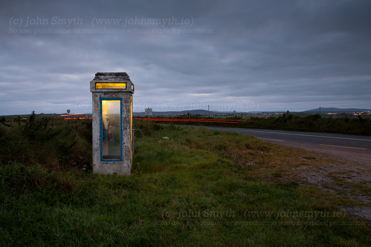 Early morning on the Mullet peninsula in Co. Mayo, Ireland [just outside Belmullet]. In this long exposure photo, the lights of a passing car streak past an old phone box. The phone was still working (I checked).