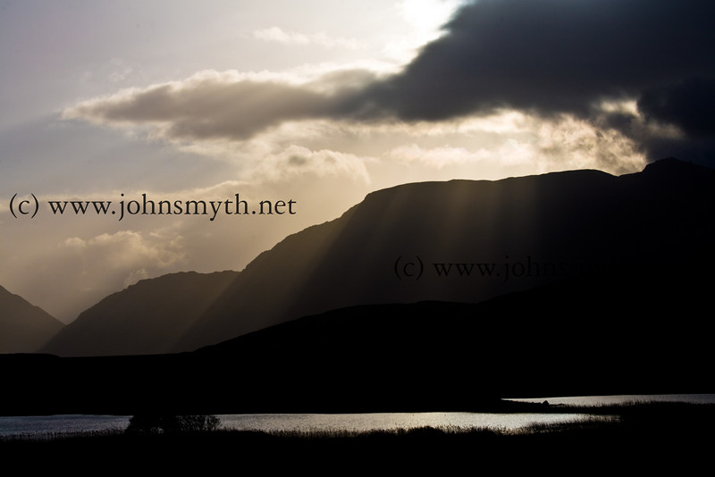 Sunbeams peer through cloud near Srahwee in Co. Mayo. In the lake in the foregound lies the stumps of an ancient forest.