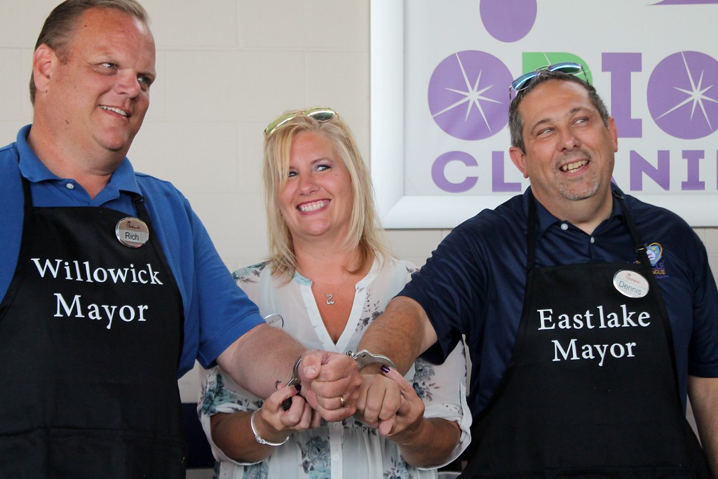 . Kristi Garabrandt - The News-Herald� <br> Chick-fil-A, Willoughby Commons owner, Billie Federer slaps a set of handcuffs on Willowick\'s  Mayor Rich Regovich and Eastlake\'s Mayor Dennis Morley after the lemon squeeze rematch.